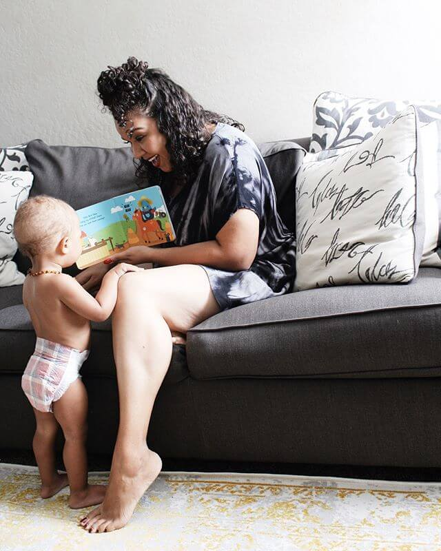 A photograph of a mother and her baby on a sofa reading a book.
