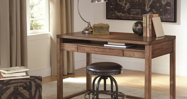 Baybrin modern contemporary rectangular wood desk with black swivel stool and gray and black striped pouf on the ground. Infront of the desk is a framed map.