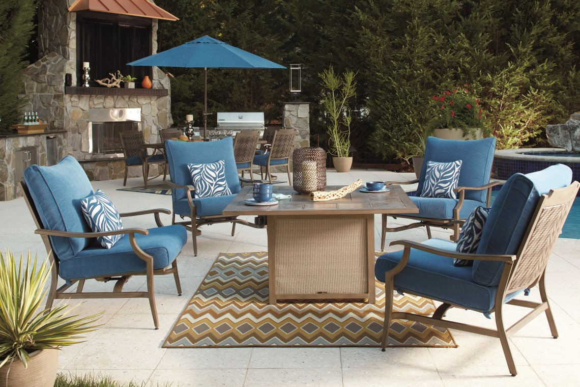 Outdoor dining set with a firepit, chairs and an outdoor kitchen in the background.