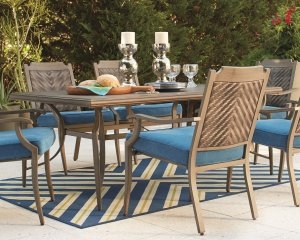 Outdoor dining table with beige chairs with blue cushions on top of a blue and green chevron rug.