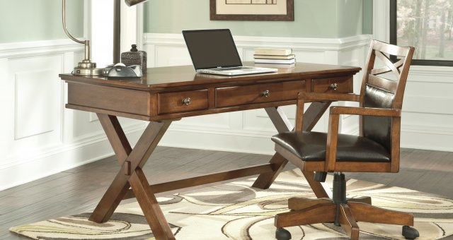 Burkesville medium brown wood modern office desk with swiveling chair and desk lamp on top of the desk. The room surrounding has light blue walls and a neutral abstract patterned rug,