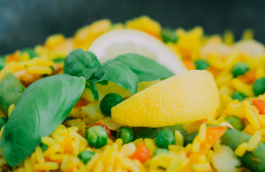 Chicken Paella made with yellow rice, vegetables and garnished with lemon slices.