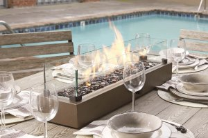 glass table top outdoor firepit on top of a wooden table with bows and wine glass around it.