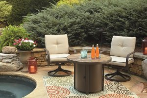 outdoor patio tile table with beige chairs with blue cushions, underneath is a blue and green chevron rug