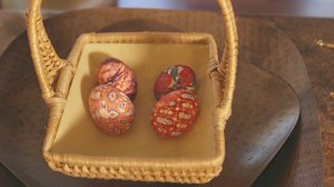 Easter basket holding tie dyes eggs on an ashley furniture homestore serving tray.