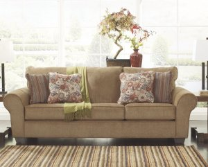 Tan sofa with decorative floral pillows and a green throw.
