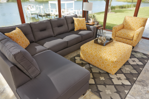 Gray sofa with yello throw pillows and yellow ottoman and chair.