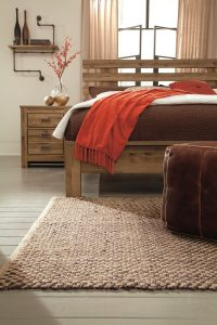 vintage aged brown finish on these open slat king headboards and nightstands in a room with a rug.
