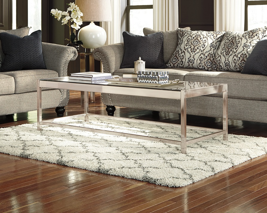 white and gray gate rug underneath a silver coffee table.