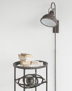 An antique looking brown wall light is ready next to a table with a pile of books