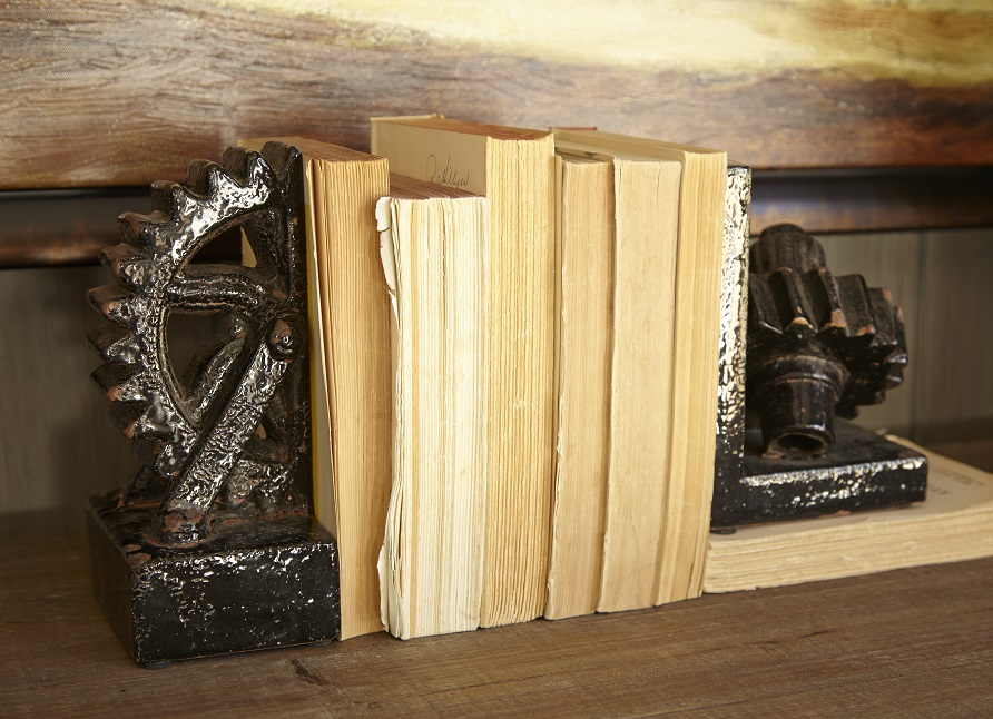 Set of two interesting bookends shaped like gears with books in between them on a table.