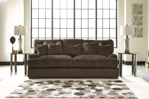 Neutral colored polka dotted rug in front of a brown plush sofa.