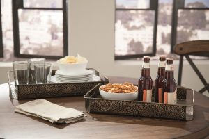 antique bronze tone metal serving trays with drinks and snacks on a coffee table with two windows in the background.