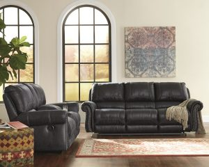black reclining sofa in a large empty room with a moroccan rug with tribal wall art on the back wall.