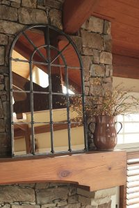 arched window design mirror on a rustic mantel.