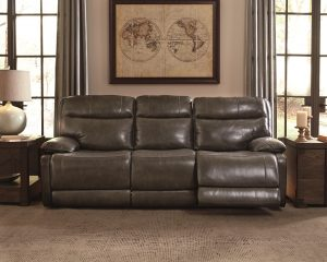 Grey leather reclining sofa in a dim light empty room with two windows and wall art of a map on the back wall.