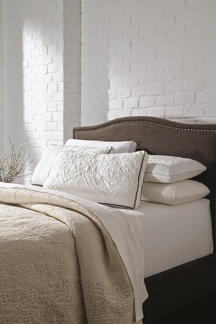 Assorted ashley pillows on an ashley mattress