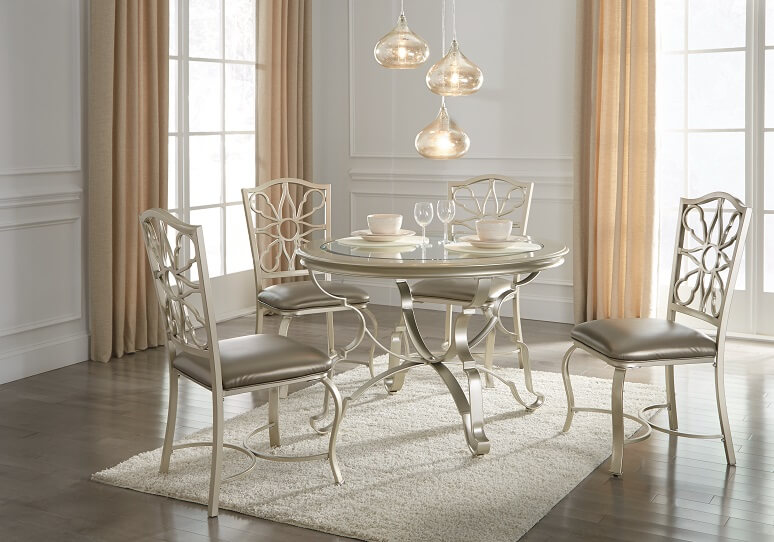 A dining table with matching dining chairs with 3 pendant lights hanging high above the table. On the table there are two bowls and two glasses. Underneath the table there is a white rug.