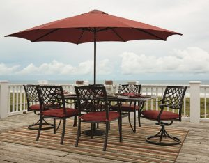 outdoor patio set with brown table and orange cushioned chairs and umbrella