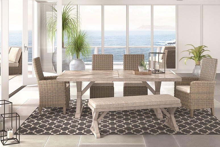 Outdoor dining room table with matching chairs. The dining room is overlooking the ocean with several indoor plants in the background. On the table is a tray with a succulent and a candle holder with a candle inside. Underneath the dining room table is a black patterned rug.