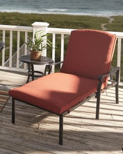 A red chaise lounge chair with cushion located on a dock over looking the ocean.