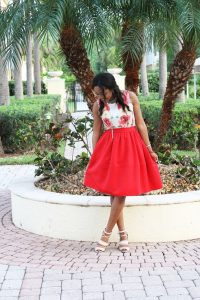 Model with red skirt and floral top standing on cobblestones in a park with palm trees behind her.