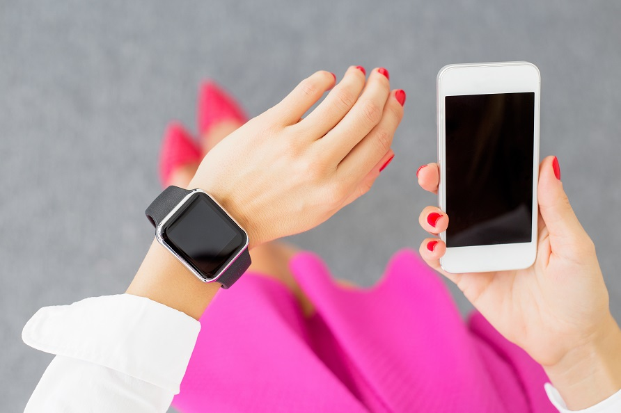 Woman with smartwatch and smartphone
