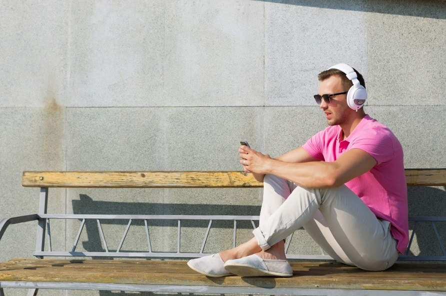 man in pink shirt listening to music on his white headphones