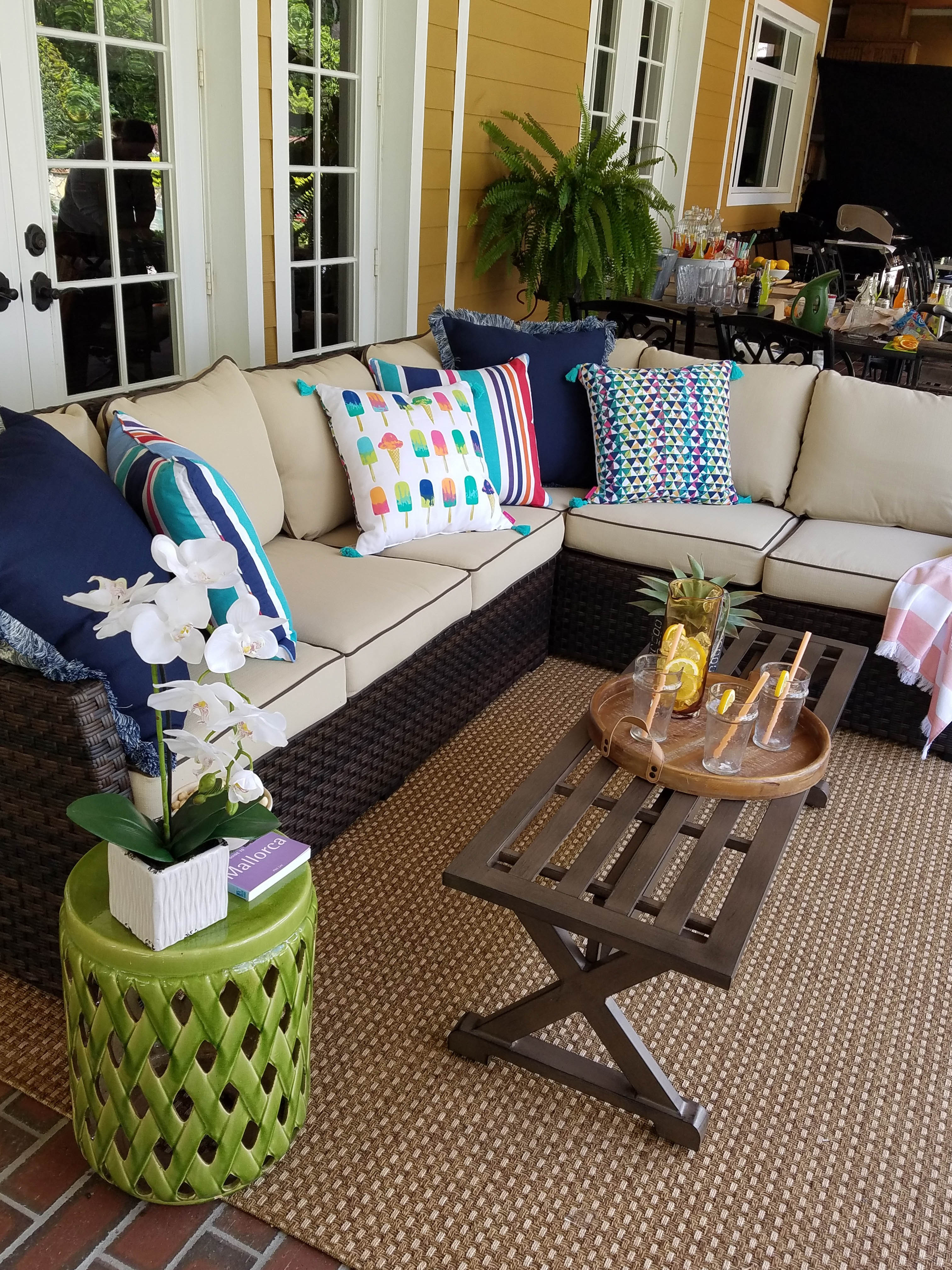 An outdoor cushioned sectional with bright and vibrant fun pillows on top. An outdoor table with a tray of lemonade on top with a small neon green side table with greenery for decoration.