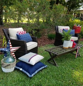 Two lounge chairs in a backyard with a outdoor table and decorative red, white and blue decor.