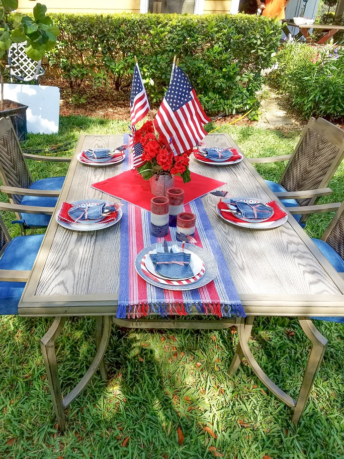 Red white and blue jean dining table set up in the backyard.