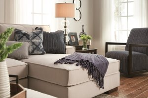 Cream colored sofa with navy blue pillows, throw blanket and chair next to it.