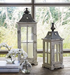 Set of two white washed candle lanterns on a table with with a window behind them overlooking ferns.