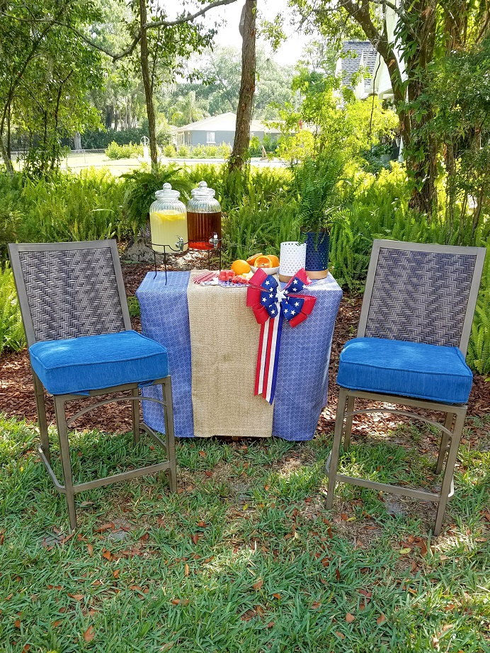 Two ashley outdoor chairs in front of a drink station in the backyard.