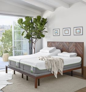 An adjustable tempur-pedic mattress on a wooden bed frame with a tall tree and throw blanket resting on the mattress.