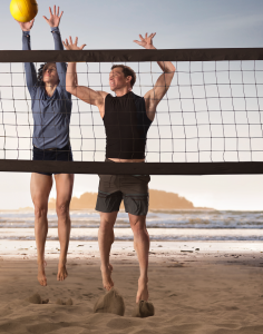 Volleyball athletes spiking a volleyball on a beach court that overlooks the ocean.
