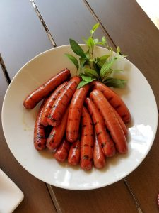 Grilled hot dogs displayed on a serving plate.