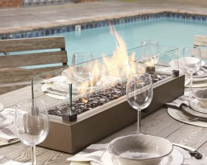 a sleek rectangular tabletop fire bowl in the center of a set table with a pool in the background.