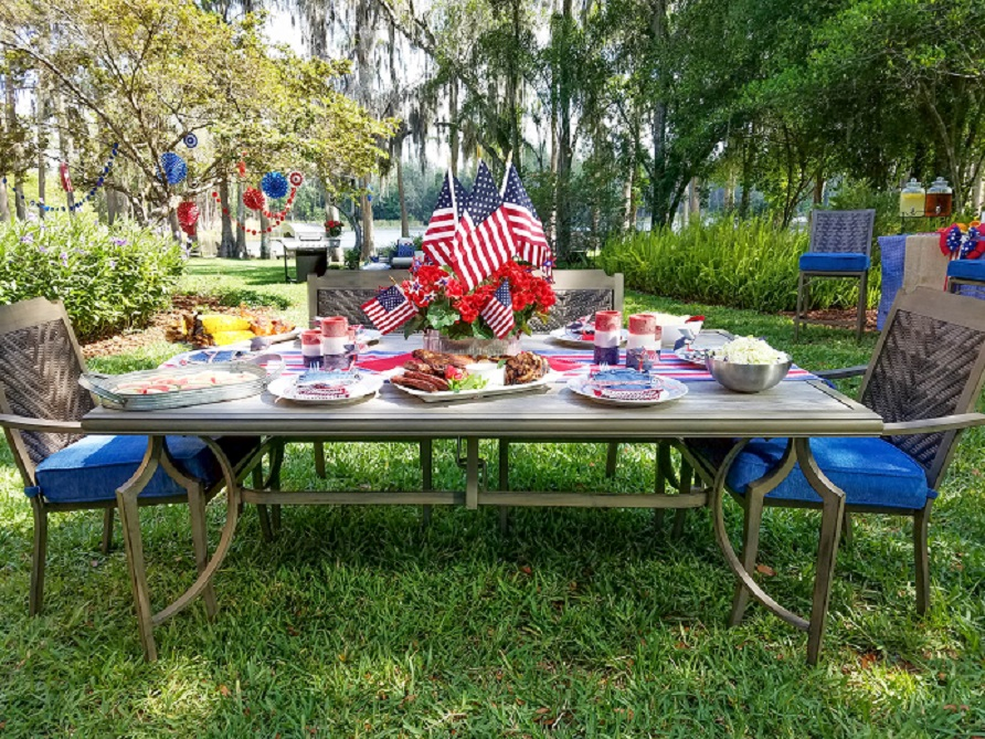 Outdoor dining table and chairs set with all kinds of food with memorial day decor.