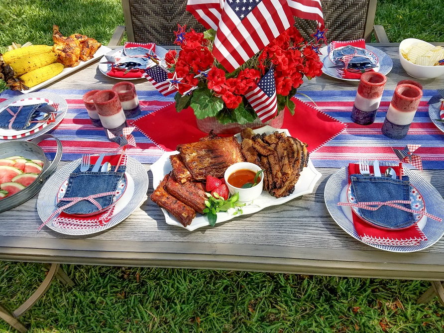Memorial day dining table set with food from the grill with patriotic theme.