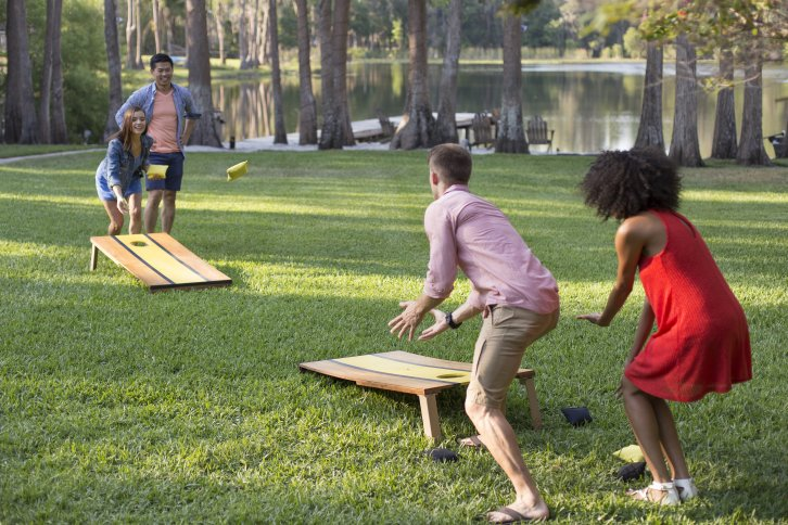 A group of kids playing corn hole in the backyard.