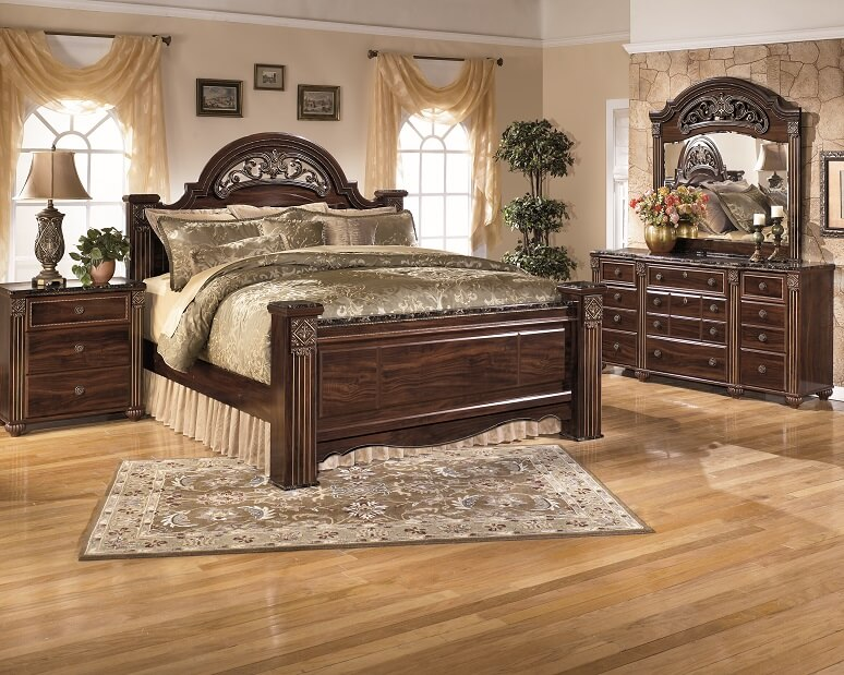 Large brown wooden poster bed with a very old school look.