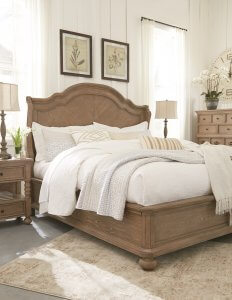 Large light brown bed with white bedding in a very natural well lit setting.