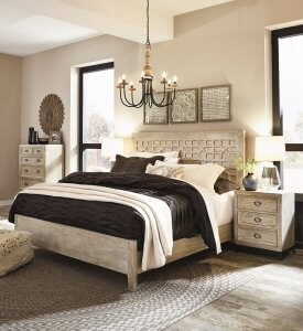 Large bedroom with cream colored wood with a chandelier hanging high above the bed and a nightstand with a lamp next to the bed.