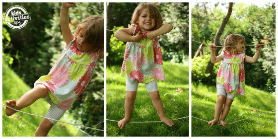 little girl playing on a diy tight rope in her yard.