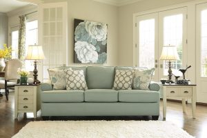 Seafoam green sofa in a white room with matching coastal decor.