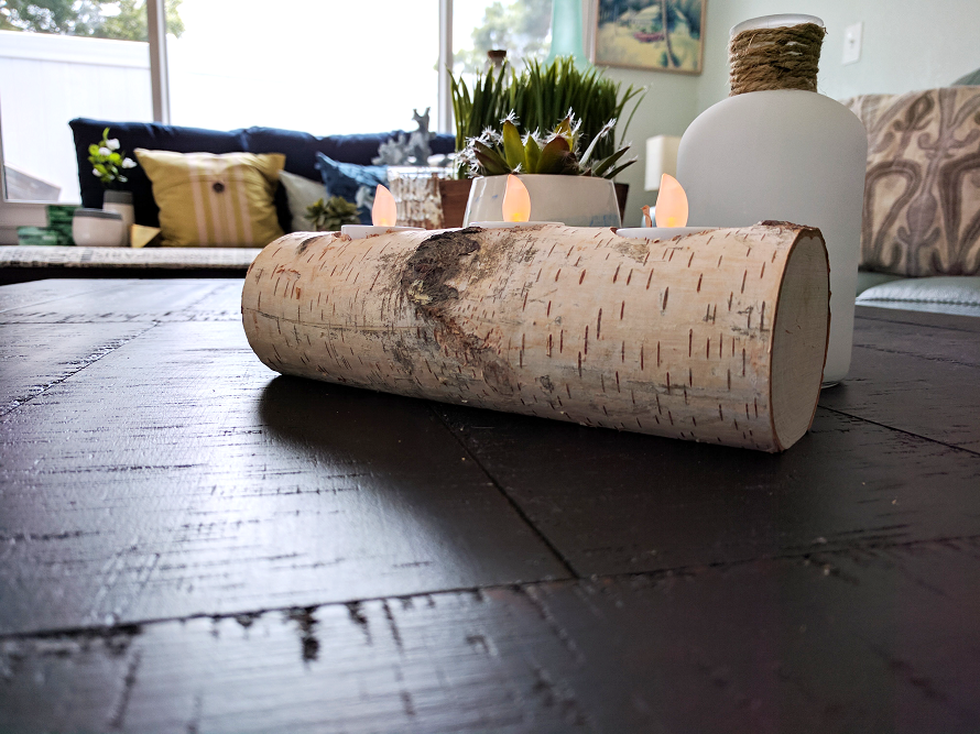 Wood log candle holder with candles inside as decoration for the coffee table.