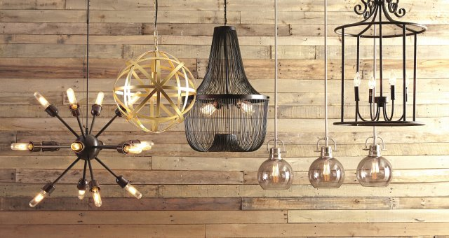 group shot of pendant lights hanging in front of rustic wood paneling.