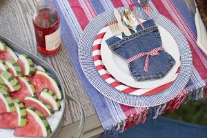 Outdoor dining table with 4th of july table setting made with denim blue jeans.
