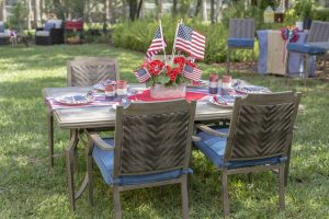 Outdoor dining table and chairs decorated for a 4th of July barbecue,